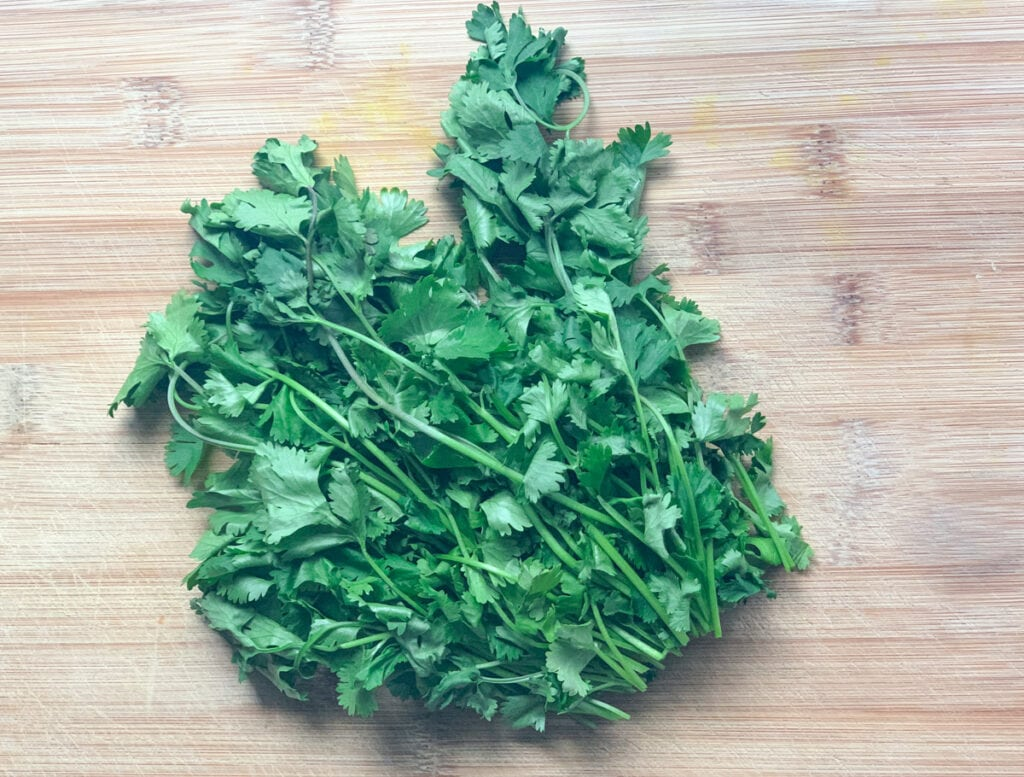 fresh cilantro on a wooden cutting board with stems removed
