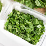 Chopped Cilantro leaves in a container lined with paper towel