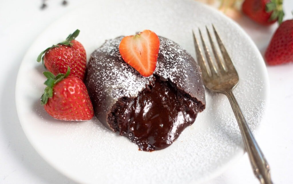 chocolate lava cake with chocolate flowing and strawberry in the top and side