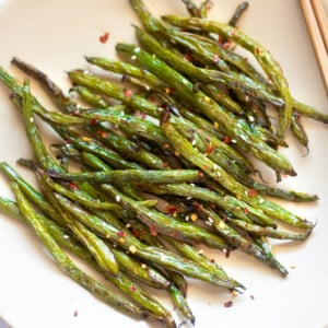 roasted garlic green beans asian style in a plate topped with sesame seeds and red pepper flakes