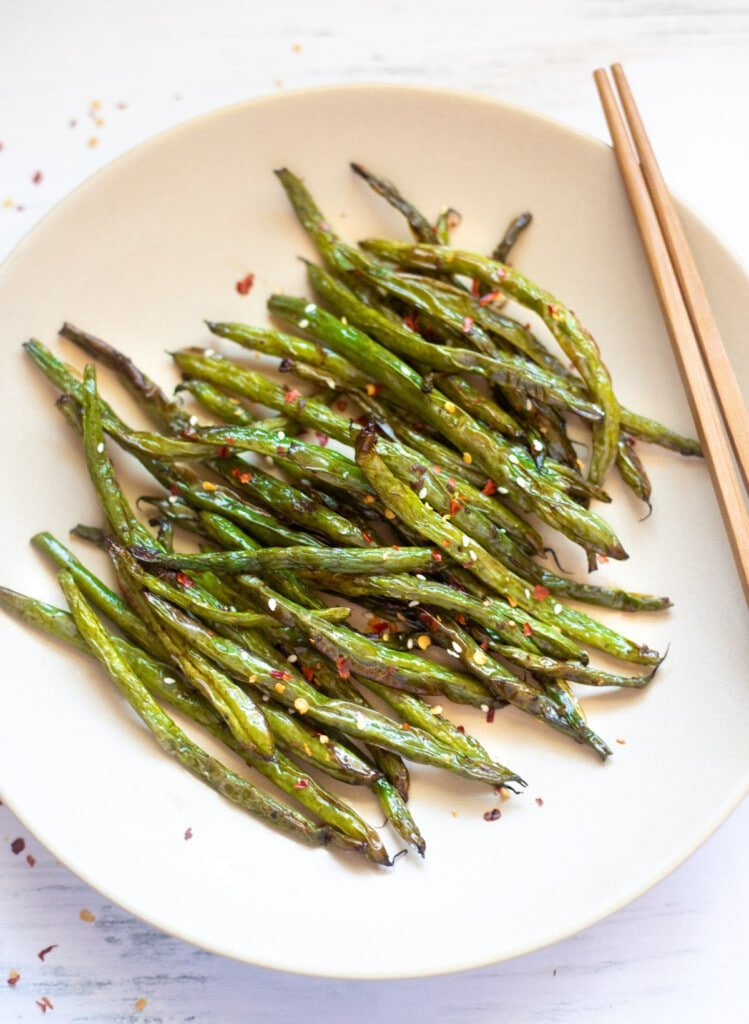 Chinese style roasted green beans with garlic on a plate with chopsticks