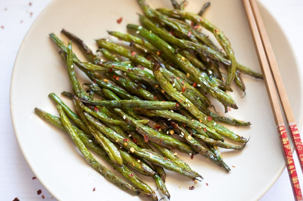 Roasted garlic green beans in a plate with chopsticks