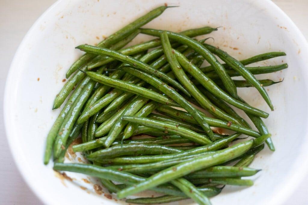 Seasoned green beans in a white bowl