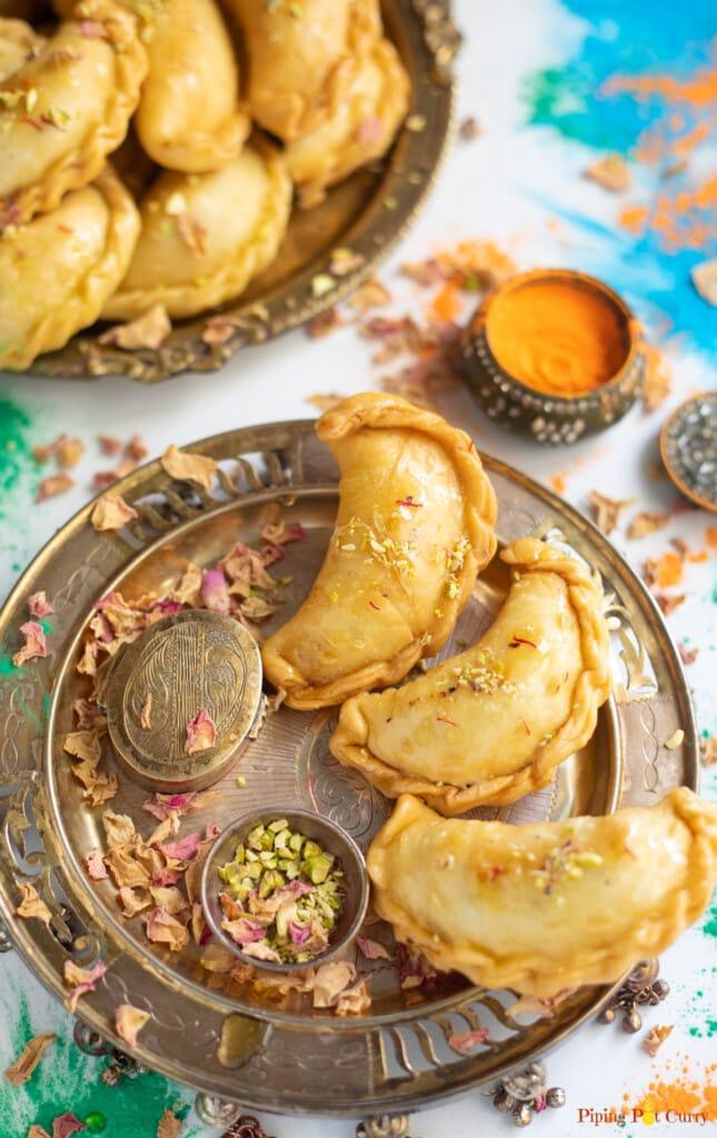 Mawa Gujiya served in a plate decorated for Holi