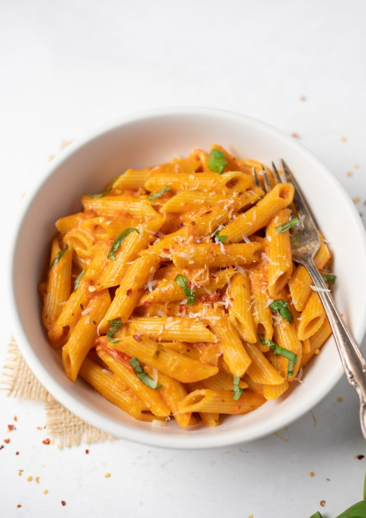 Creamy homemade penne pasta in a white bowl garnished with basil and parmesan