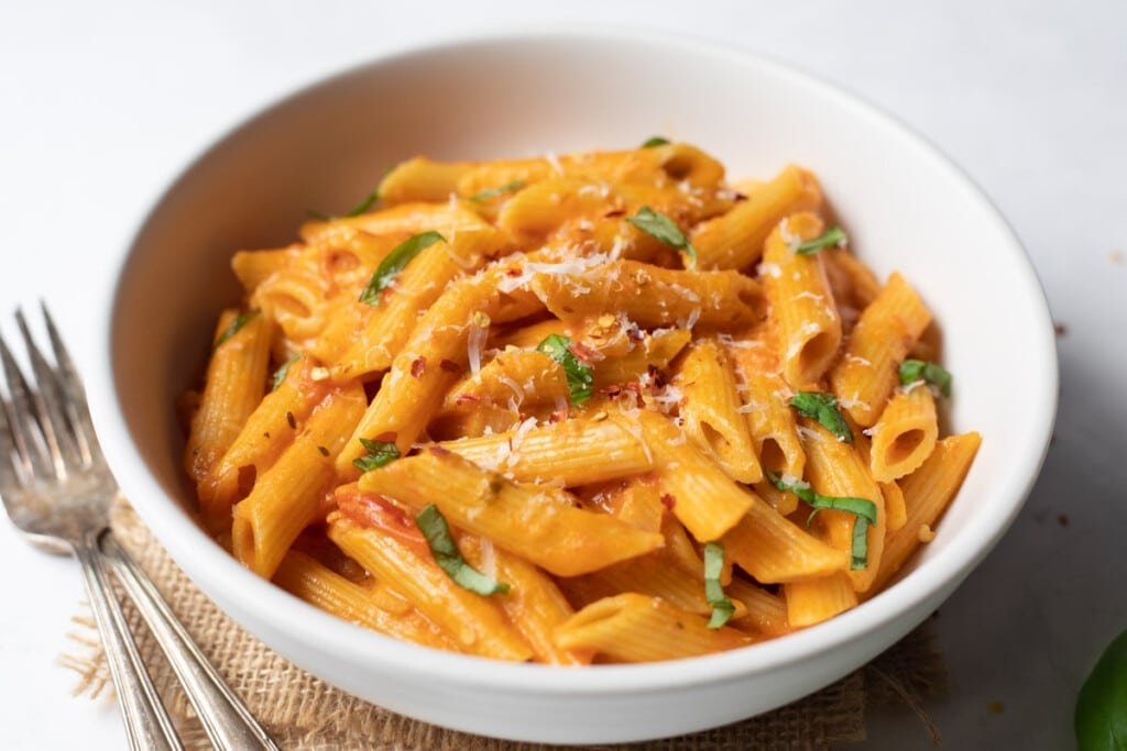 Penne alla vodka in a white bowl garnished with basil