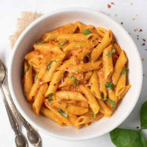 Creamy penne alla vodka pasta in a white bowl garnished with basil and parmesan