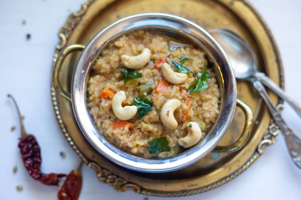 Bisi Bele Bath with means hot lentil rice in a bowl topped with cashews and tempering