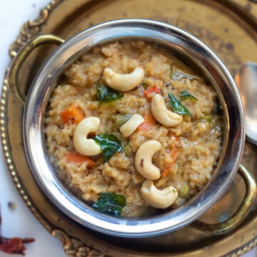 Bisi Bele Bath - How Spicy lentils and rice in a pretty bowl garnished with tempering and cashews.