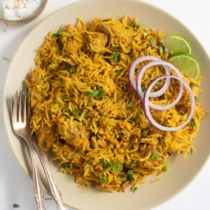 chicken biryani served on a plate garnished with cilantro, onions and lime