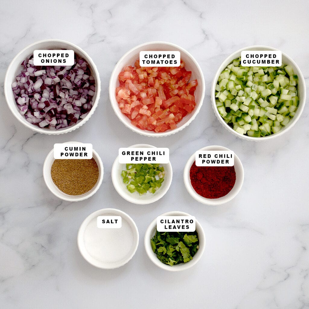 ingredients such as tomato, onion, cucumber along with spices in small bowls