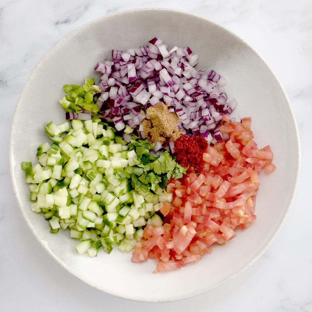 punjabi salad ingredients such as cucumber, tomato, onion and spices in a white bowl