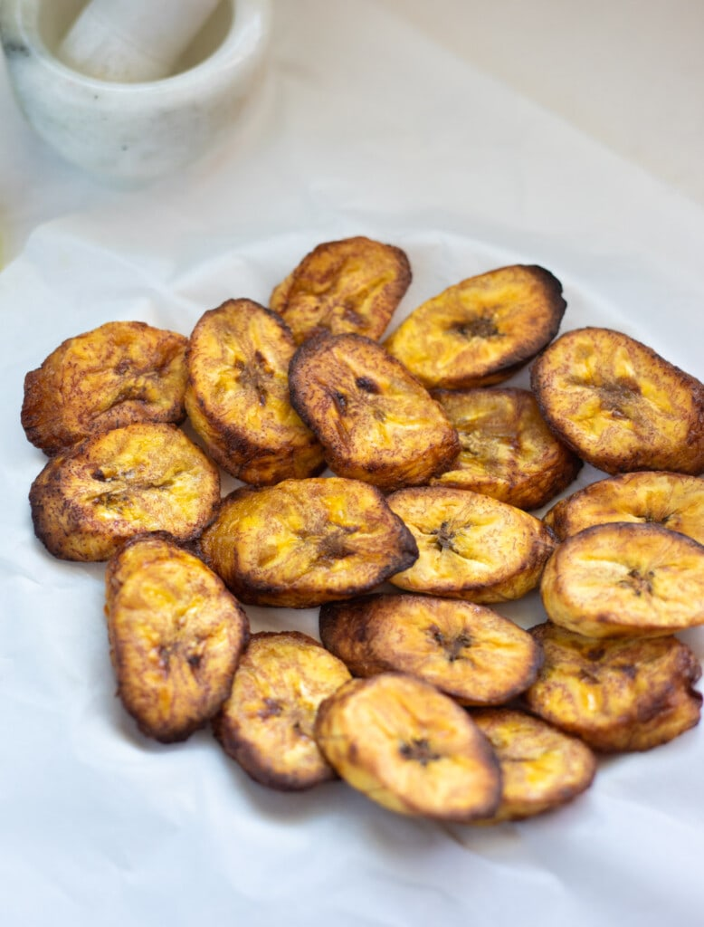 air fried plantains served in a plate over parchment paper