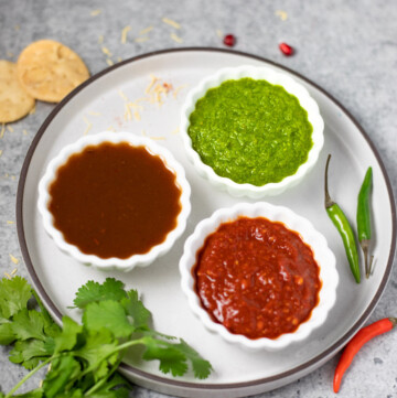 3 Indian dipping sauces in small bowls - green chutney, tamarind chutney, red chili garlic chutney