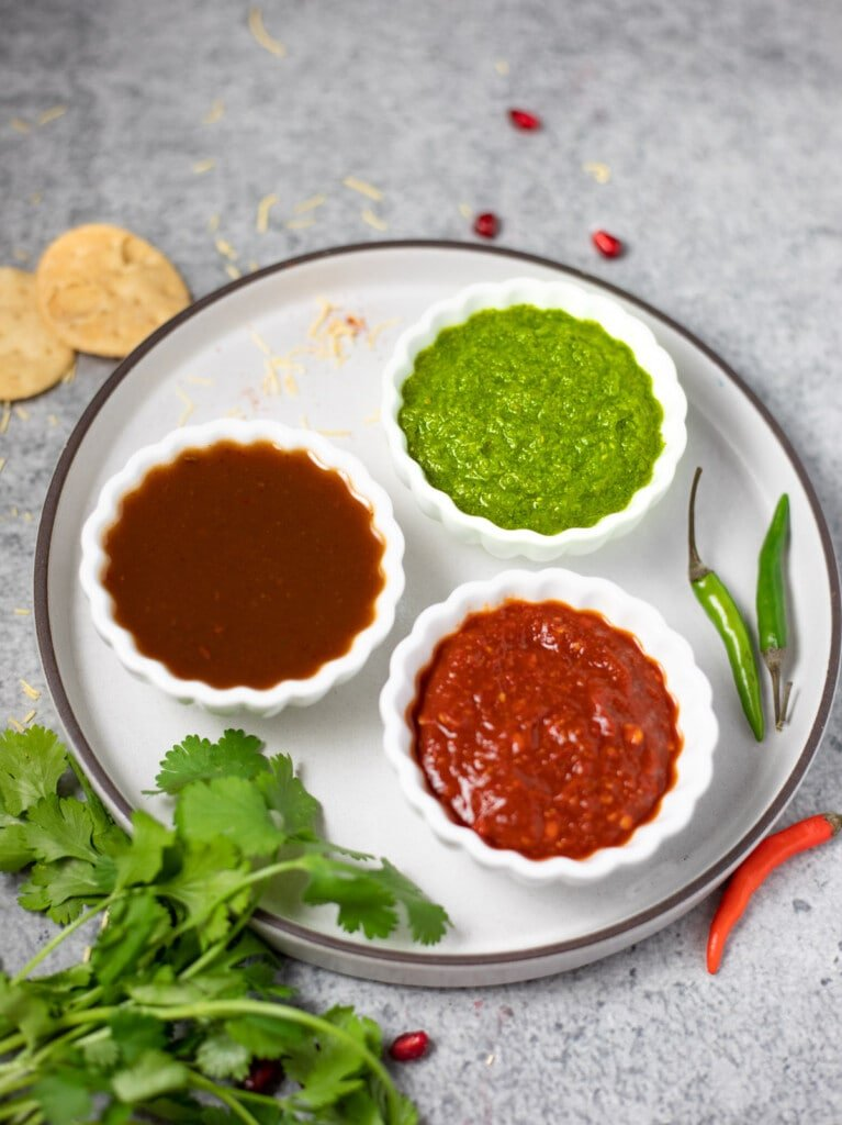 3 Indian dipping sauces in small bowls - green chutney, tamarind chutney, red chili garlic chutney