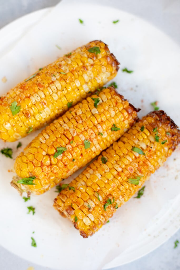 Spicy roasted corn on the Cobb on a plate garnished with cilantro