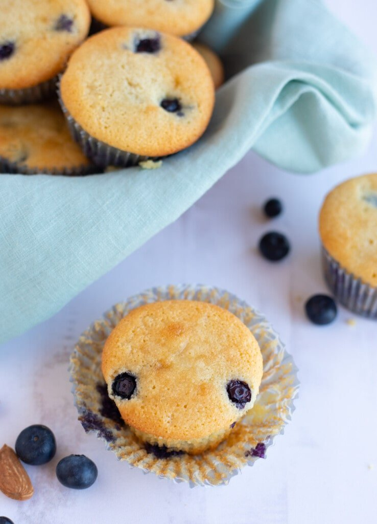 Light and moist blueberry muffin on a white table with more muffins in a basket