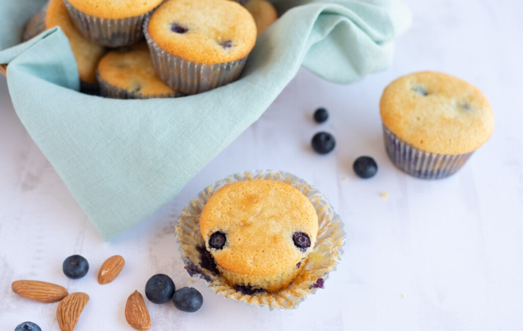 Flourless Low Carb blueberry Muffin with the muffin liner opened and some almonds and blueberries on the side.