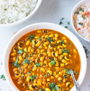 Black eyed peas curry in a bowl garnished with cilantro and rice and yogurt on the side