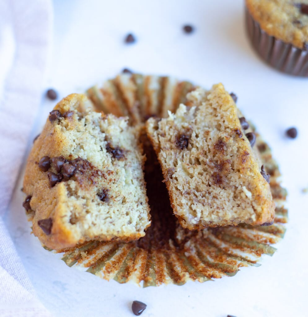 Soft Moist Banana Muffin with chocolate chips cut in two pieces.