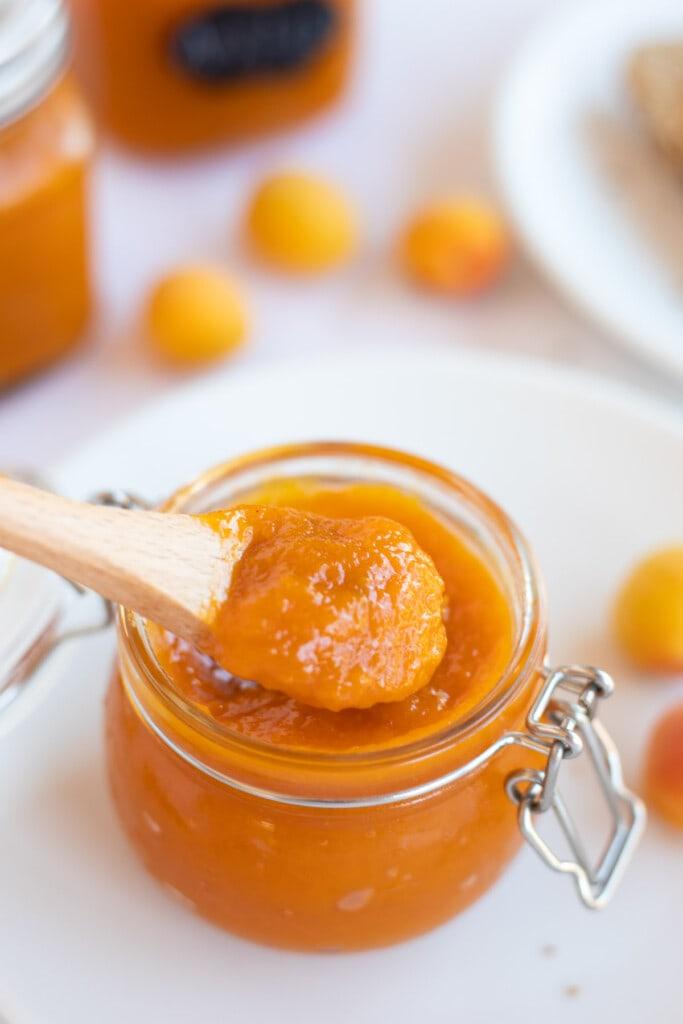 Delicious apricot jam being taken out from a glass mason jar by spoon