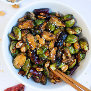 Asian style kung pan Brussels sprouts in a bowl with chopsticks