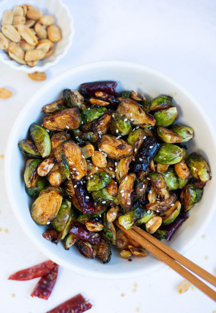 PF Changs style king pao Brussels sprouts in a bowl with chopsticks and peanuts on the side