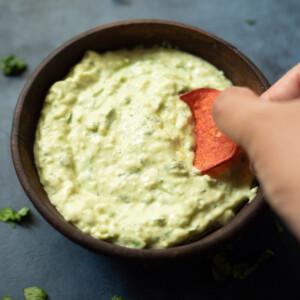 Dipping a chip in Avocado cilantro jalapeno crema sauce