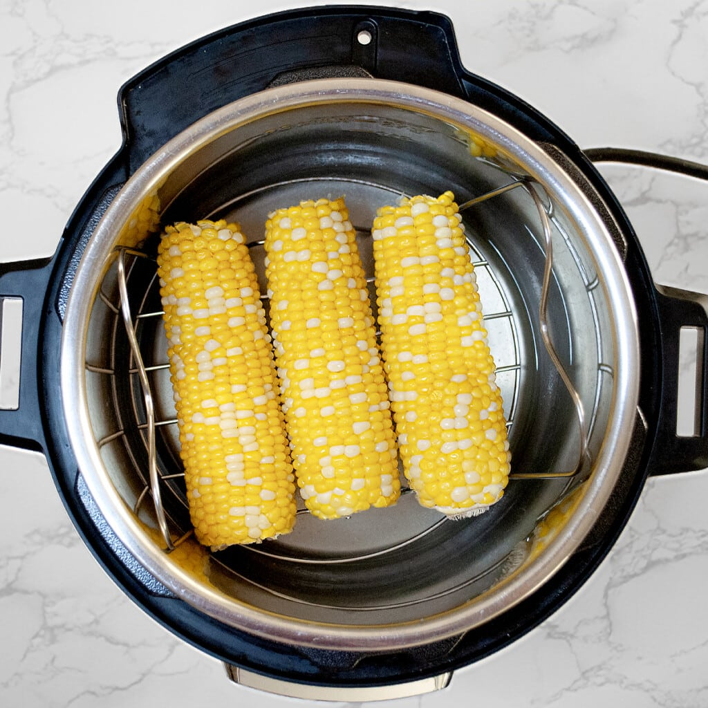 corn on the cob being cooked in the instant pot