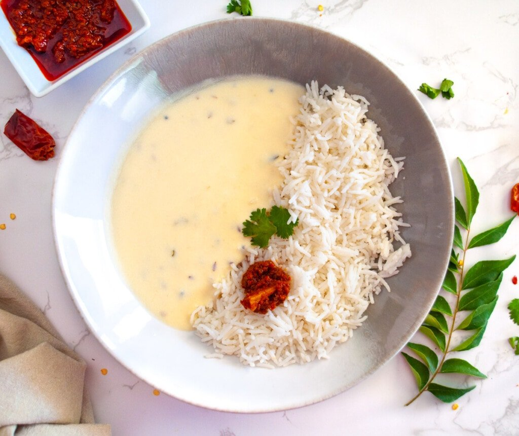 Gujarati kadhi served with rice and pickle in a bowl