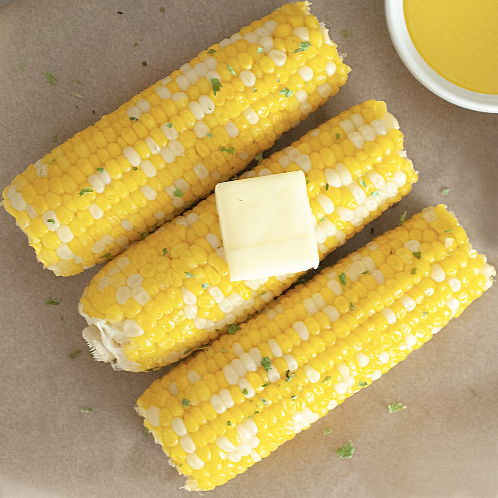 closeup of corn on the cob with butter and parsley