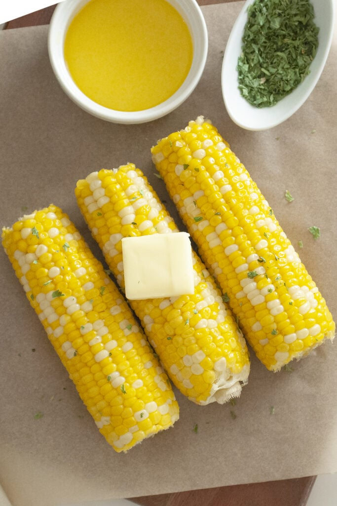 Corn on the cob slathered with butter and garnished with parsley