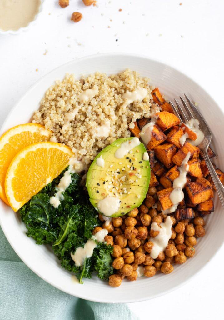Sweet potato chickpea quinoa buddha bowl topped with avocado and sliced oranges