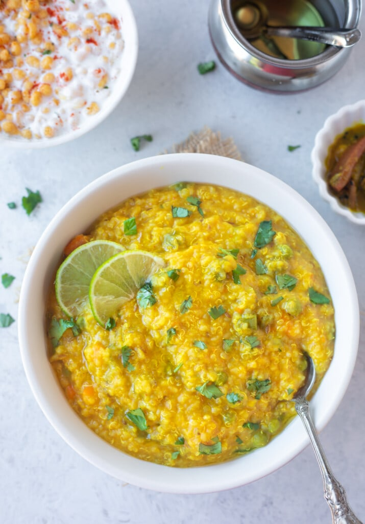 Delicious quinoa Khichdi in a bowl garnished with cilantro and lime, with ghee, pickle and yogurt on the side.