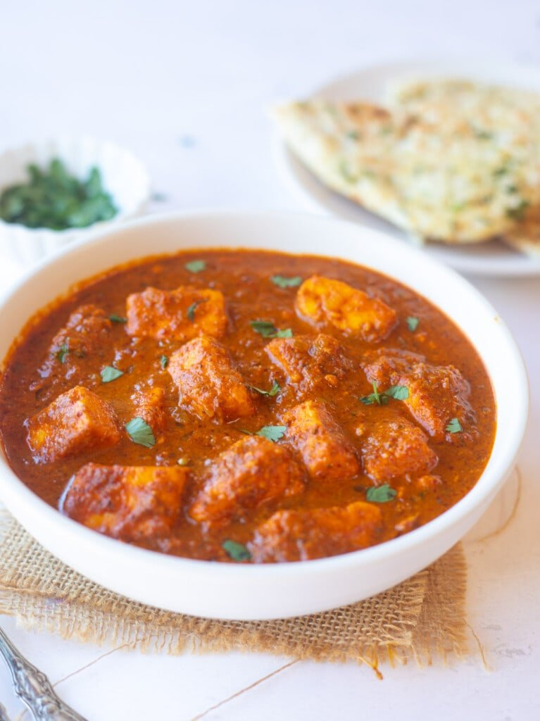 Paneer vindaloo curry in a white bowl with naan in the back.