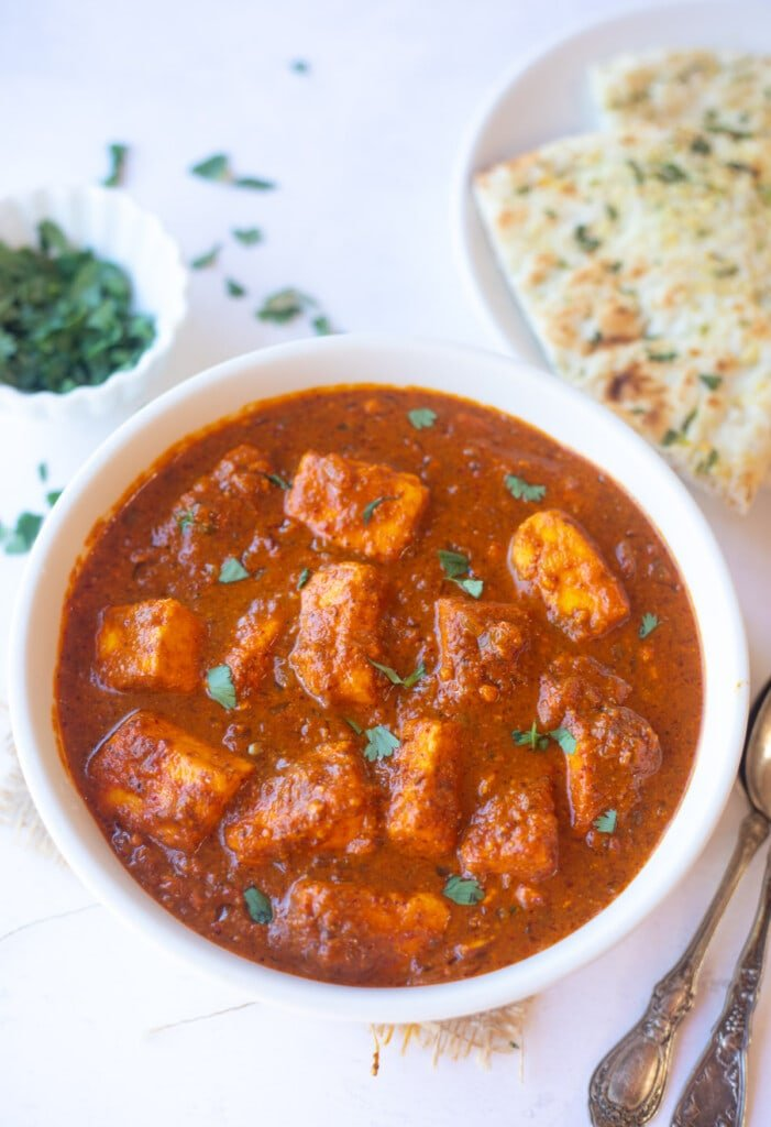 Vegetarian paneer vindaloo curry in a bowl garnished with cilantro