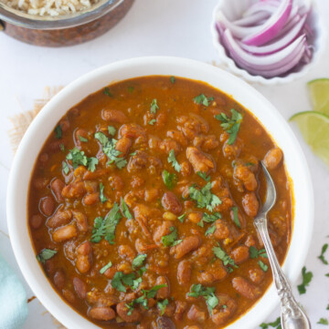 Rajma Masala in a bowl garnished with cilantro and rice and onions on the side